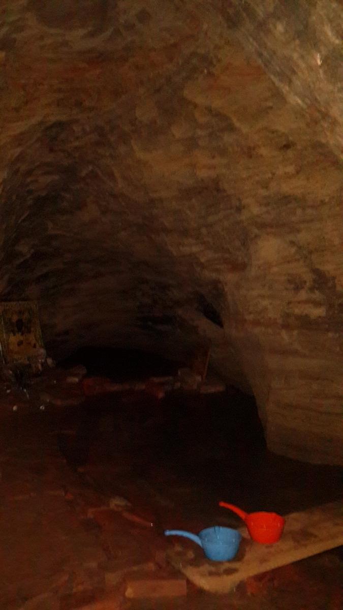 В Доложской пещере. Озеро и пластмассовые ковшики для святой воды.