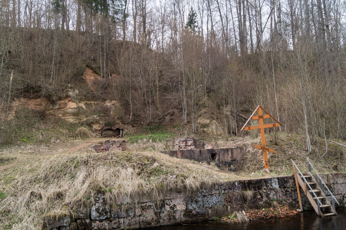 У Доложской пещеры. Крест на берегу Долгой на месте Успенской церкви.