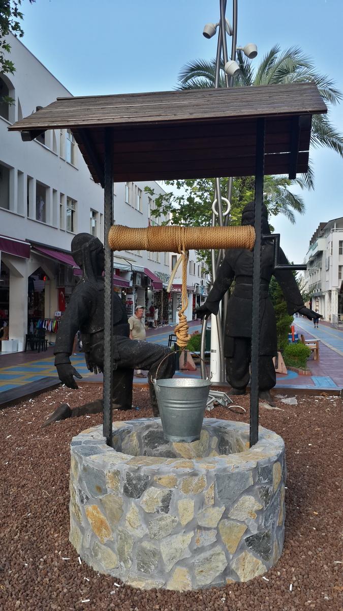Кемер. Городская скульптура. Объяснение у колодца.
